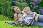 Young mother and her little son having rest in spring park — Stock Photo