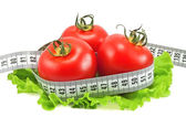Tomatoes with tape measure and lettuce — Stockfoto
