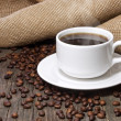 Stock Photo: Cup of coffee and coffee beans on old wooden table