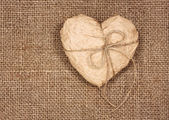 Paper heart on a burlap — Stockfoto
