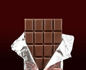 Chocolate bar with open cover — Stock Photo