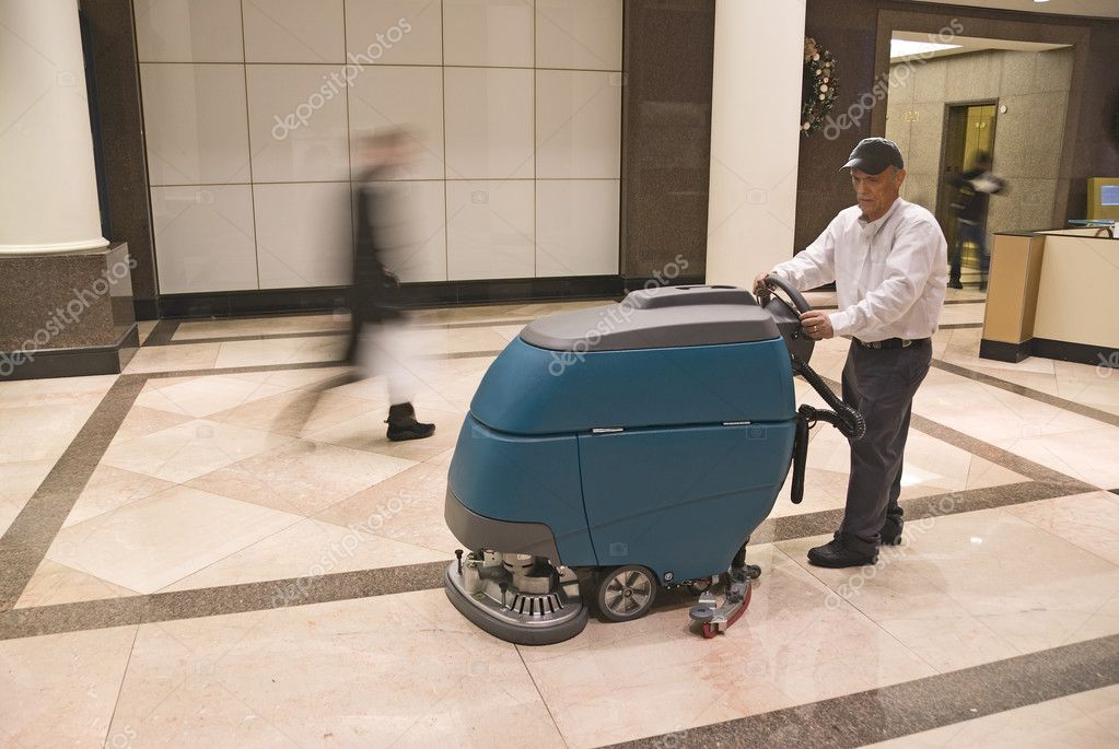 Floor cleaning machine operator in commercial building lobby — Stock Photo #10383841