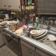 Dirty dishes piled up in sink - Stockfoto