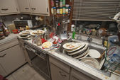 Dirty dishes piled up in sink — Stockfoto