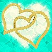 Or coeur en forme d'anneaux sur bokeh turquoise représentant l'amour et — Photo