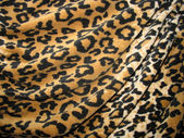 Fleecy brown draped leopard skin fabric — Stock Photo