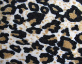 Fleecy white and brown leopard skin fabric background — Stock Photo