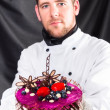Stock Photo: Handsome confectioner with cake against dark background