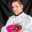 Handsome confectioner with cake — Stock Photo