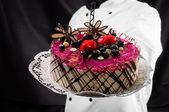Holding cake against dark background — Stock Photo