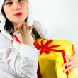 Girl giving a big kiss and a present - Stock Photo