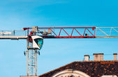 Big industrial crane against blue sky building a house — Stock Photo