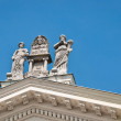 Foto de Stock  : Romstatues on roof against blue sky