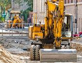 Big excavators at urban construction site — Stock Photo