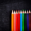 Colorful pencils against black chalkboard - ストック写真