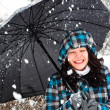 Stock Photo: Young womwith umbrellin blizzard