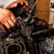 Hands of a worker repairing broken engine — Stock Photo