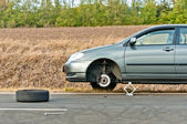 Car without tire on the road — Stockfoto