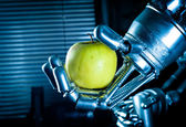 A robot hand holding a fresh apple — Stock Photo