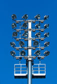 Stadium lighting with a lot of reflectors against blue sky — Stock Photo