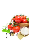 The branch of cherry tomatoes in a wooden bowl, onion, garlic, b — Foto de Stock