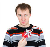 A disgruntled man holding a small gift isolated on white backgro — Stock Photo