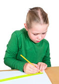 Klein meisje tekening op een witte tafel. — Stockfoto