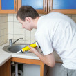 Plumber putting a silicone sealant to installing a kitchen sink — Stock Photo #9439439