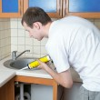 Royalty-Free Stock Photo: Plumber putting a silicone sealant to installing a kitchen sink