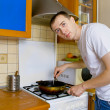 Young man preparing food in the kitchen — Stock Photo