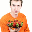 Young man holding a strawberry isolated on white background. — Stock Photo