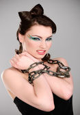 Young brunette with chain and makeup — Stock Photo