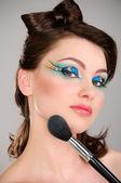Beautiful girl makes a makeup — Stock Photo