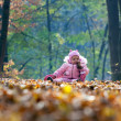 Funny baby playing with leaves in park — Foto Stock
