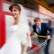 Bride and groom riding on shopping cart — Stock Photo