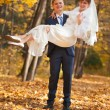 Stock Photo: Groom carries his bride