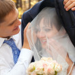 Groom protecting beautiful bride from rain — Stock Photo