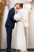 Bride and groom kissing against fountain — Stock Photo