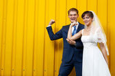 Bride and groom posing against yellow wall — Stock Photo