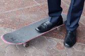Businessman standing on skateboard — Stock Photo