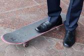 Businessman standing on skateboard — Stock Photo
