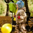 Baby boy in autumn leaves holding balloon — Stockfoto