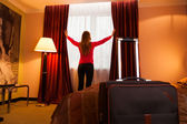 Young woman in a hotel opening window — Stock Photo