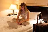 Junge frau mit laptop im hotel — Stockfoto