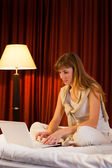 Young woman using laptop in hotel — Stock Photo