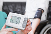Blood pressure check for young adult in wheelchair. — Stock Photo