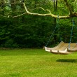 Swing bench in lush garden — Stock Photo