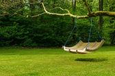качели скамейке в пышном саду — Стоковое фото