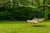 Swing bench in lush garden — Stok fotoğraf