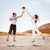 Couple jumping to catch a ball — Stock Photo